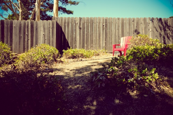 red plastic chair in front of fence
